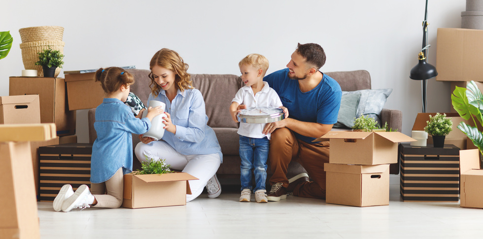 happy family mother father and children move to new apartment and unpack boxes